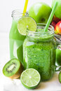 Jar Mug With Green Vegetable Smoothie, Bottle With Fruit Juice, Scattered Kiwi, Limes, Apples Stock Images - 87672374