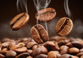 Closeup Falling Coffee Bean With Smoke On Brown Background Royalty Free Stock Photos - 87736318