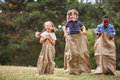 Children Competing At Sack Race Royalty Free Stock Photo - 87806585