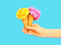 Hand Holding Two Ice Cream Cone With Flowers Over Blue Stock Photos - 87807943