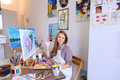Girl Sits On Stool At Easel And Writing Painting, Uses Brush To Royalty Free Stock Photography - 87814067