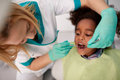 Female Dentist Repair Tooth To Black Child Royalty Free Stock Photography - 87882507