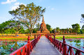 Beautiful Scenery Scenic View A Red Bridge Crossing Traphang-Trakuan Lake To The Ancient Buddhist Temple Ruins Of Wat Sa Si In The Stock Photo - 87910440
