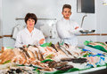 Two Sellers Posing Near Display With Frozen Fish Stock Photos - 88157613