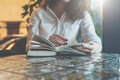 Close-up Of Paper Book, Notebook, Diary On Table In Cafe. Businesswoman In White Shirt Sitting At Table And Reading Book Stock Photography - 88198482
