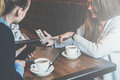 Two Young Business Women Sitting At Table And Using Smartphones.Woman Showing Colleague Graphs On Smartphone Screen. Royalty Free Stock Image - 88200256