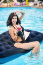 Smiling Female In Black Bikini Holding A Cocktail Sitting On Mattress In Swimming Pool On A Blurred Background Of Resort Royalty Free Stock Photo - 88269775