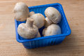 Fresh Champignons In Blue Plastic Bowl On A Wooden Chopping Board Royalty Free Stock Image - 88292496