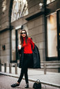 Young Stylish Girl, Passing By The Windows.Wearing Fashionable Glasses And A Black Coat.Keeps Coffee. Stock Photo - 88499230