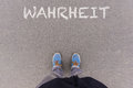 Wahrheit, German Text For Truth Text On Asphalt Ground, Feet And Royalty Free Stock Photos - 88566238