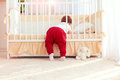 Cute Toddler Baby Climbing Into The Cot In Nursery Room At Home Royalty Free Stock Photos - 88569628