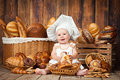 Small Child Cooks A Croissant In The Background Of Baskets With Rolls And Bread. Stock Image - 88603841