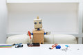 Robot Sits At A Table And Holds A Screwdriver Lying Next To A Ro Royalty Free Stock Photography - 88947567