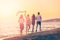 Group Of Happy Young People Is Running On Background Of Sunset Beach And Sea Royalty Free Stock Image - 88956876