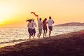 Group Of Happy Young People Is Running On Background Of Sunset Beach And Sea Royalty Free Stock Image - 88958936