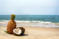 Coconuts And Pineapples On The Sand By The Sea Stock Photography - 89040642