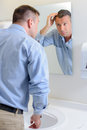 Man Looking At Hair In Mirror Royalty Free Stock Images - 89109199