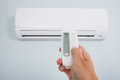 Person Operating Air Conditioner With Remote Control Royalty Free Stock Image - 89190716