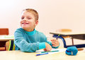 Cute Boy With Special Needs Writing Letters While Sitting At The Desk In Class Room Stock Photo - 89398040