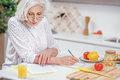 Serious Old Housewife Reading Document In Kitchen Stock Photography - 89536792