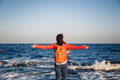 Young Happy Girl With Orange Backpack Standing On A Seaside Breathing Fresh Air Raising Arms Enjoying The View Royalty Free Stock Photography - 89602787