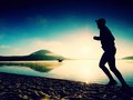 Silhouette Of Sport Active Man Running On The Lake Beach At Sunrise. Healthy Lifestyle. Stock Image - 89883231