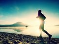 Silhouette Of Sport Active Man Running On The Lake Beach At Sunrise. Healthy Lifestyle. Stock Photo - 89883310
