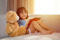Smiling Asian Chinese Little Girl Reading Book With Teddy Bear Stock Photo - 89945730