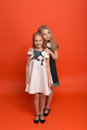 Two Sisters In Beautiful Stylized Dresses On A Red Background In Stock Photos - 89988873