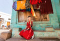 Village House And Young Woman Sitting At Front Of Colorful Building In Small Indian Town. Royalty Free Stock Photos - 90042718
