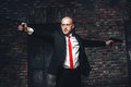 Bald Hired Killer In Red Tie Aims A Pistols Royalty Free Stock Photography - 90159877
