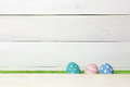 Three Colorful Handmade Easter Eggs Stand On A Green Lawn, Covered With A Barrier, On A White Wooden Background With Space On The Royalty Free Stock Photo - 90215985