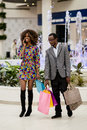 Pretty Afro-american Couple In A Shopping Mall. Woman Talking On A Phone And Man Carrying Bags. Stock Images - 90272374