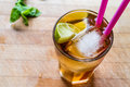 Long Island Iced Tea Cocktail With Lime, Ice And Served With Pink Straw Stock Images - 90335884