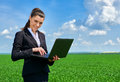 Business Woman In Green Grass Field Outdoor Work On Laptop. Young Girl Dressed In Black Suit. Beautiful Spring Landscape With Clou Royalty Free Stock Photography - 90342037