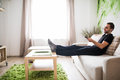 Young Man Using Remote Control While Sitting On Couch In Living Room Stock Images - 90452374
