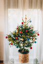 A Small Christmas Tree In A Pot, Decorated With Balls, Garlands Royalty Free Stock Images - 90615439