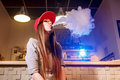 Young Pretty Woman In Red Cap Smoke An Electronic Cigarette At The Vape Shop Royalty Free Stock Image - 90748076