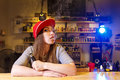 Young Pretty Woman In Red Cap Smoke An Electronic Cigarette At The Vape Shop Stock Images - 90748444