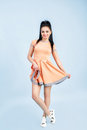Smilling Young Brunette Woman In Orange Dress On Blue Background. Royalty Free Stock Images - 90800279