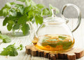 Herbal Tea In A Transparent Teapot On The Table And Sprigs Of Fresh Melissa Lemon Balm And Mint Stock Photography - 90956512