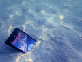Mobile Phones On The Sand Under The Sea Water. Stock Image - 90981961