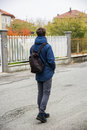Teenage Boy Walking Alone In Street With Backpack Royalty Free Stock Photos - 90990958