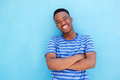 Smiling Young African American Man Leaning Against Blue Wall Royalty Free Stock Photos - 91440748
