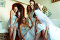 Bridesmaids Help Bride To Put On Shoes While She Sits On The Sof Stock Photography - 91447432