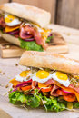 A Sandwich With Bacon, Cheese And Fried Quail Eggs. A Sandwich With Fresh Vegetables And Herbs On A Wooden Background. Stock Photography - 91511482