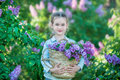 Smiling Little Cute Blonde Child Girl 4-9 Years With A Bouquet Of Lilac In The Hands In Jeans And Shirt Stock Images - 91779234