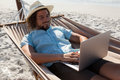 Man Relaxing On Hammock And Using Laptop On The Beach Stock Images - 91797044