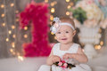 Cute Baby Girl 1-2 Year Old Sitting On Floor With Pink Balloons In Room Over White. Isolated. Birthday Party. Celebration. Happy B Royalty Free Stock Photography - 91798777