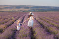 Young Beautiful Lady Mother With Lovely Daughter Walking On The Lavender Field On A Weekend Day In Wonderful Dresses And Hats. Royalty Free Stock Images - 91837029
